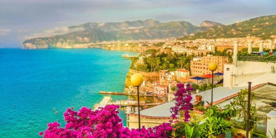Vista de Sorrento com mar, flores e cidade ao funo
