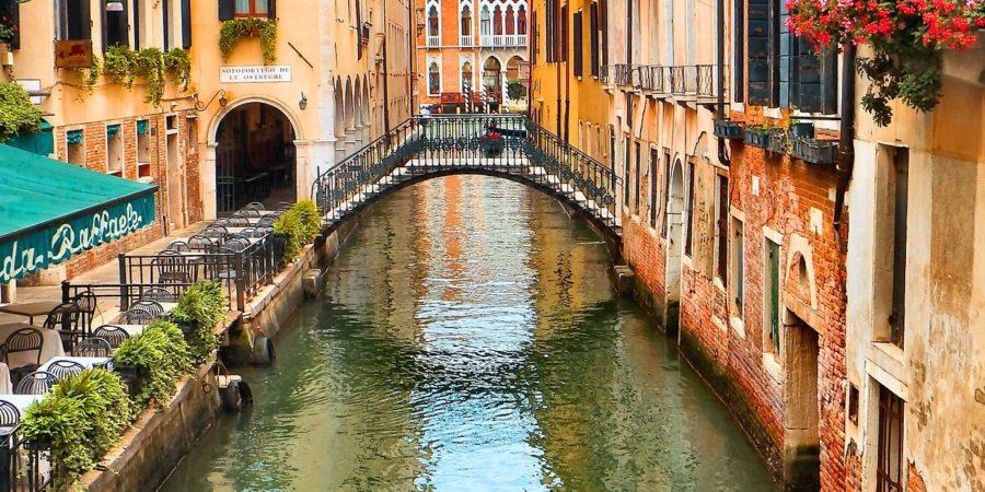 Canal romântico em Veneza, com casas coloridas e sacadas com flores