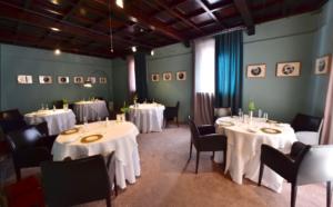 Sala de jantar sóbria com mesas e obras de arte no Osteria Francescana, um restaurante Michelin na Itália