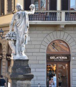 Fachada da gelateria Santa Trinita em Florença, com estátua da ponte santa Trinita em primeiro plano
