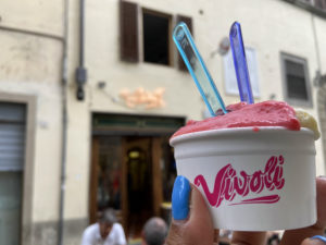 Gelato italiano segurado por uma mão em frente à Vivoli, na cidade de Florença, itália