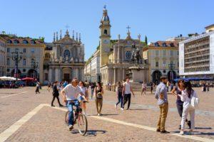 PIazza San Carlo em Turim, com pessoas caminhando e passeando de Bicicleta, num dia de céu azul