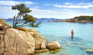 Mulher dentro de um mar azul transparente, com rochas em primeiro plano, na Costa Smeralda, Sardenha
