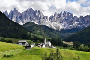 Vista da cadeia de montanha das Dolomitas, na itália, com cidade e campos verdes em primeiro plano
