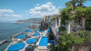 Vista panorâmica com piscina e mar do hotel bellevue syrene em sorrento