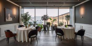 Mesas e ambiente elegante do restaurante Enrico Bartlini al MUDEC em Milão