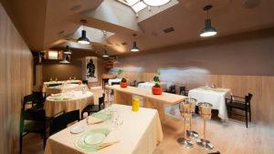 Ambiente com mesas, cadeiras e decoração do Joia, um dos melhores restaurantes de Milão