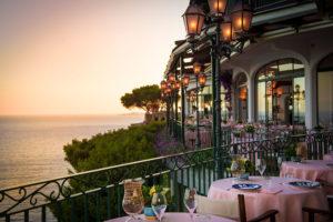 mesas, decoração e vista do mar no restaurante zass em posutano, um do slocais onde comer na costa amalfitana